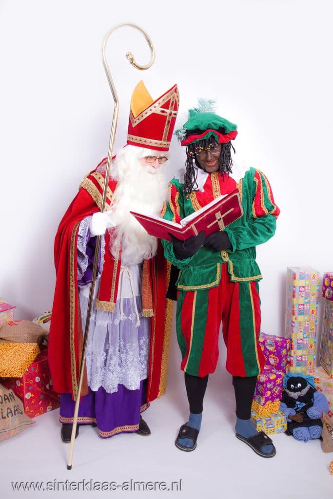 Sint en Piet bestuderen het grote boek van Sinterklaas